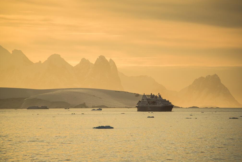 Une lumière dorée couvre les sommets pointus de l'Antarctique. Devant, le bateau de croisière a l'air minuscule.