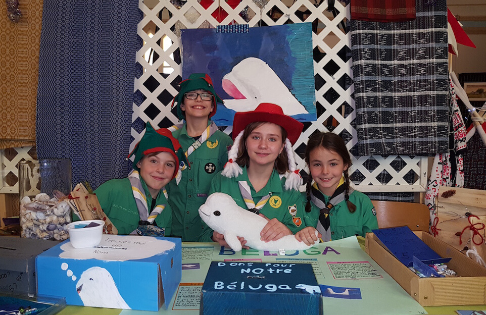 Quatre scouts devant un kiosque avec des dessins de bélugas